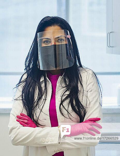 Porträt einer Ärztin mit Gesichtsmaske und Gesichtsschutz
