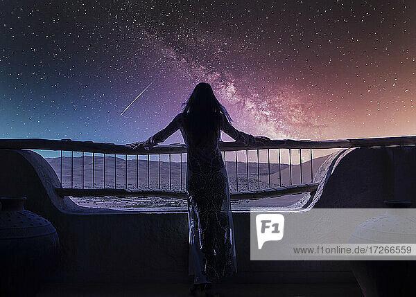 Dubai  Vereinigte Arabische Emirate  Frau in Luxus-Resort in der Wüste beobachten Sternschnuppe am Sternenhimmel in der Nacht