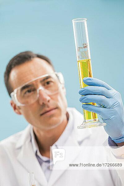Wissenschaftler schaut auf gelbe Flüssigkeit im Messbecher