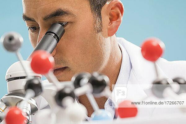 Nahaufnahme eines Wissenschaftlers  der durch ein Mikroskop schaut  Molekülmodell im Vordergrund