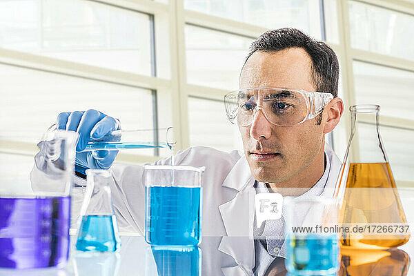 Wissenschaftler gießt blaue Flüssigkeit im Labor