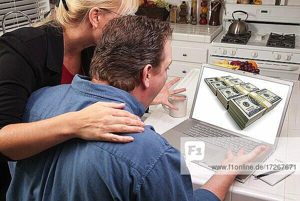 Ehepaar in der Küche mit Laptop mit Stapeln von Geld auf dem Bildschirm