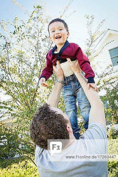 Glücklicher kaukasischer Vater hat Spaß mit seinem gemischtrassigen Babysohn