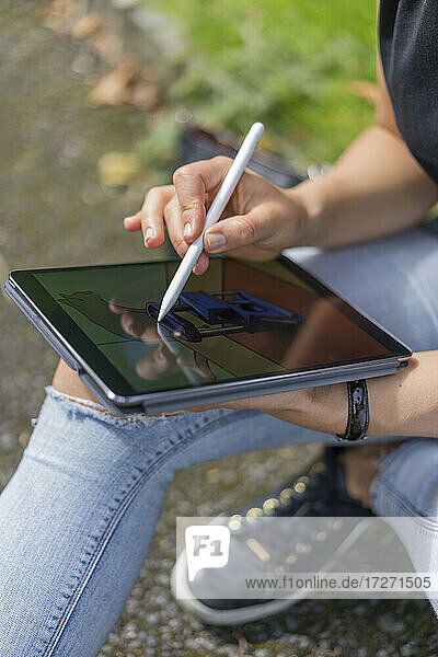 Hands of young woman drawing on digital tablet while sitting in park