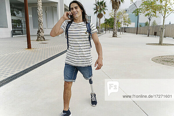 Man with artificial limb talking on smart phone while walking in city