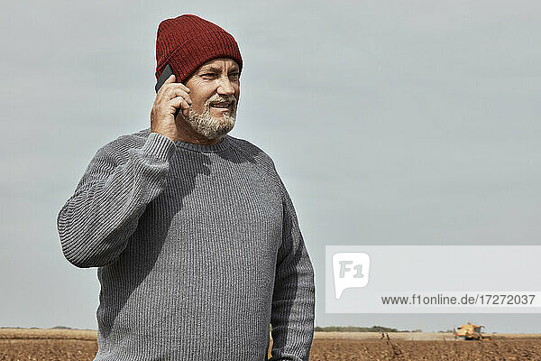 Farmer talking on mobile phone while standing at farm