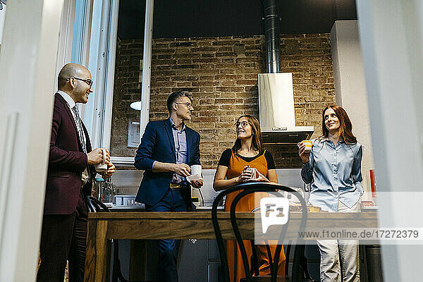 Low angle view of male and female entrepreneurs discussing while having coffee in office kitchen