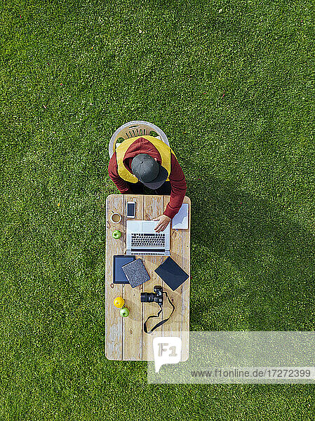 Aerial view of man working on laptop at coffee table set on green lawn