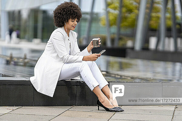 Businesswoman drinking coffee while using mobile phone outdoors