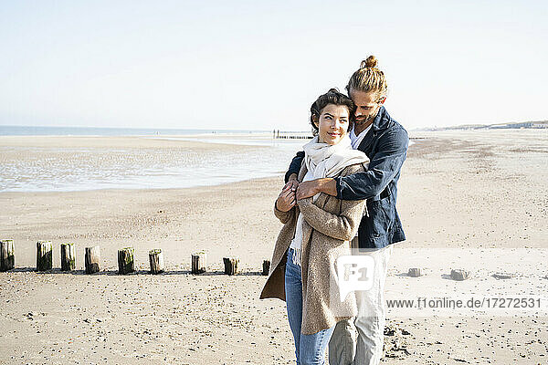 Romantic young couple embracing while standing at beach