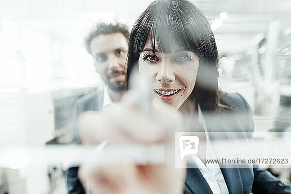 Confident businesswoman planning with male colleague at industry