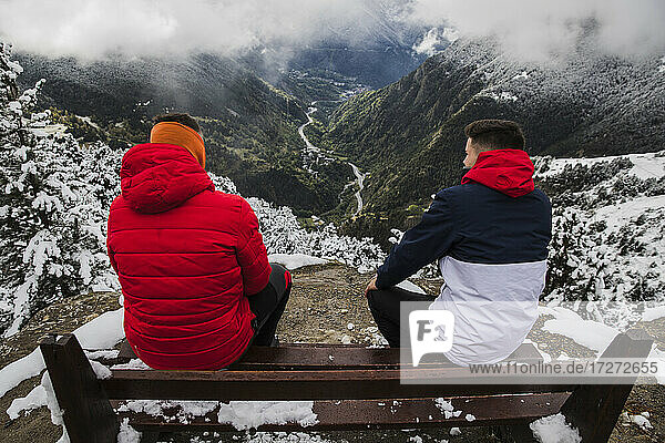 Friends spending leisure time sitting on bench during winter