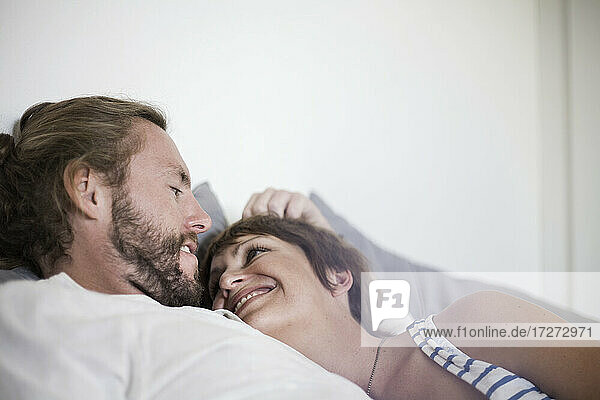 Smiling heterosexual couple resting on bed at home in bedroom