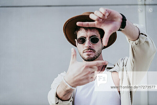 Thoughtful man in hat and sunglasses gesturing against wall