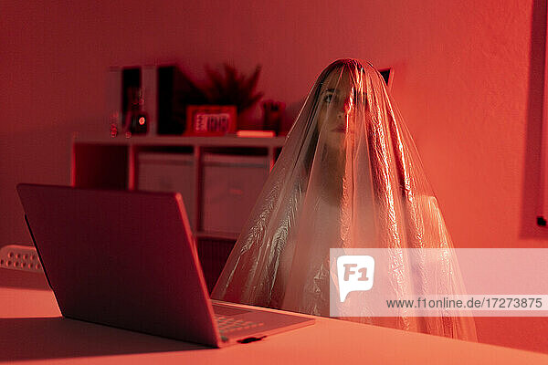 Thoughtful woman covered in plastic sitting with laptop at desk in home office during pandemic