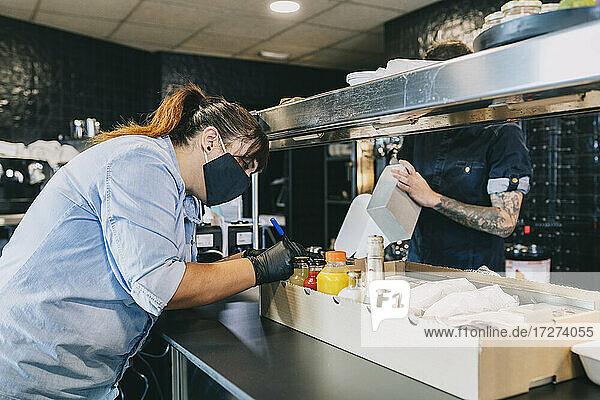Weibliche Köchin  die auf eine Box zum Mitnehmen schreibt  während ihr Kollege an der Küchentheke im Restaurant steht