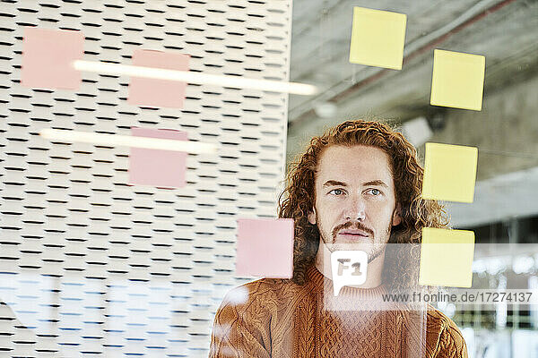 Man looking at adhesive notes stick on glass material at home