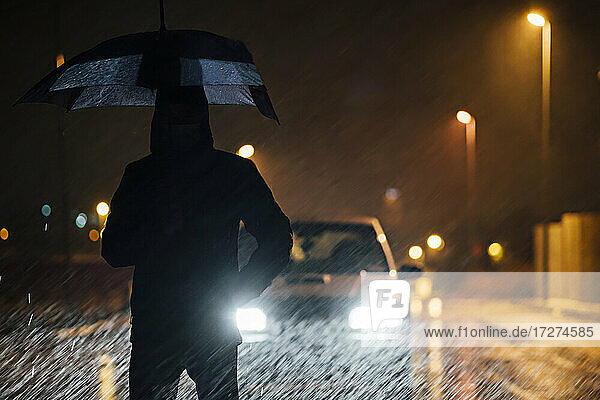 Young man with umbrella standing in front of car dutimng a rainy night