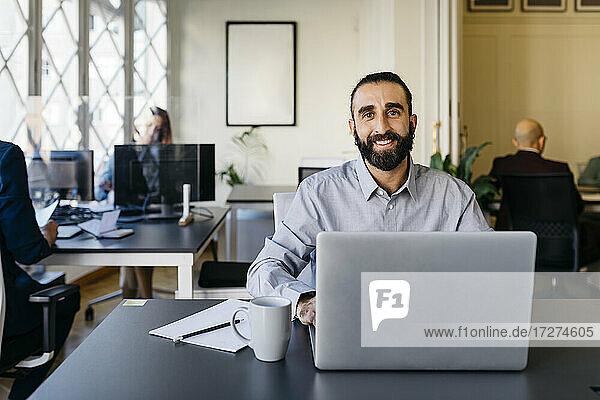 Confident hipster entrepreneur working on laptop at desk in office