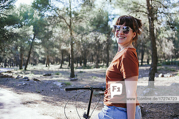 Smiling young woman in sunglasses with bicycle at countryside during weekend