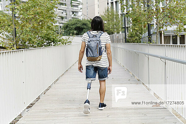 Amputed man with backpack walking on bridge in city