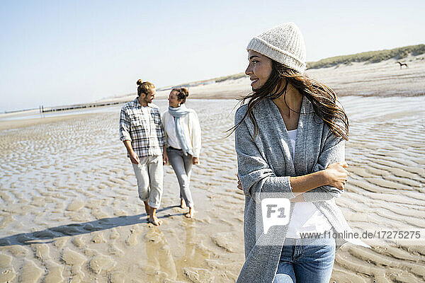 Woman looking over shoulder to man and mother walking in background at beach