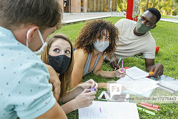 Male and female students wearing safety mask while discussing on grass in university campus