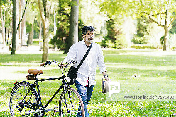Mature man with bicycle walking on grass in public park
