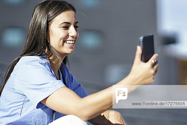Smiling doctor using mobile phone while sitting on staircase against hospital