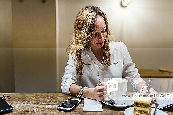 Unternehmerin schreibt in ein Notizbuch  während sie am Tisch Kaffee trinkt