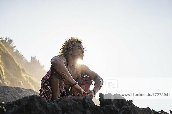 Young man looking away while crouching on rock at beach against sky