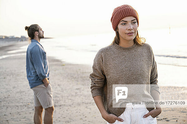 Beautiful young woman standing with hands in pockets against boyfriend at beach during sunset
