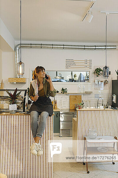 Female owner talking on smart phone sitting near counter in coffee shop