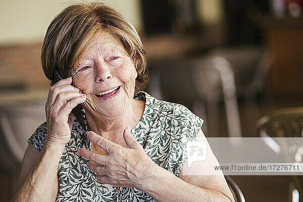 Happy woman talking on mobile phone while sitting at cafe