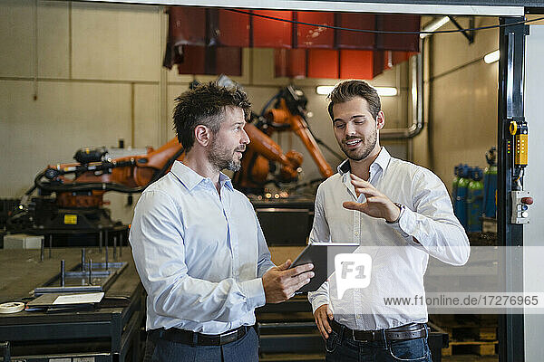 Businessmen with digital tablet discussing while standing against robotic arm machine at factory