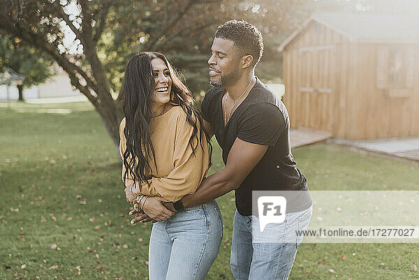Man embracing woman from behind while standing at backyard