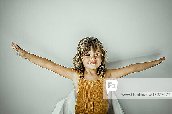Little girl with arms outstretched standing against wall at home