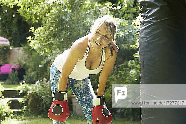 Senior woman bending over wearing boxing glove standing in back yard
