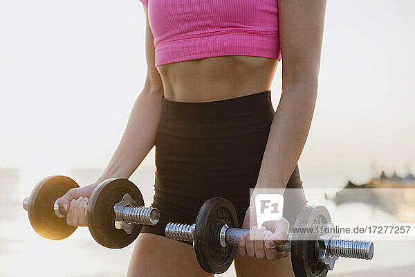 Athlete picking dumbbell while standing against sea