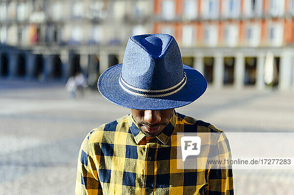 African man wearing hat while standing in city