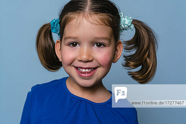 Girl smiling while standing against blue background