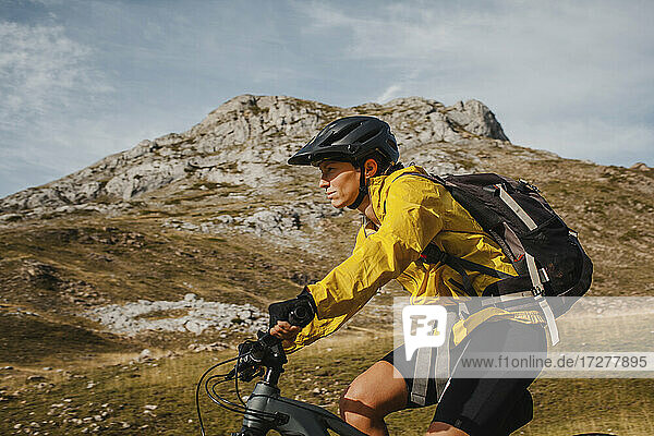 Mid adult woman with backpack riding electric bicycle on mountain at Somiedo Natural Park  Spain