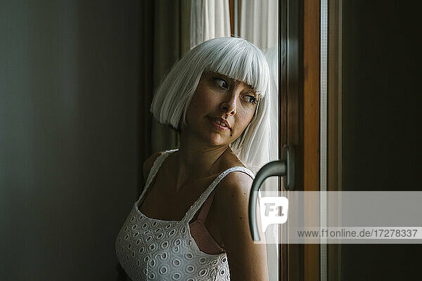 Young woman looking through window while leaning by door at home