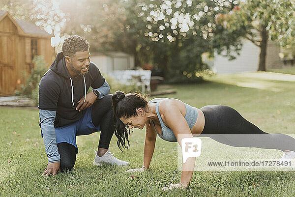 Smiling man looking at woman doing push ups at backyard