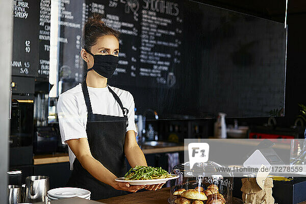 Female barista wearing protective mask while serving pasta in coffee shop