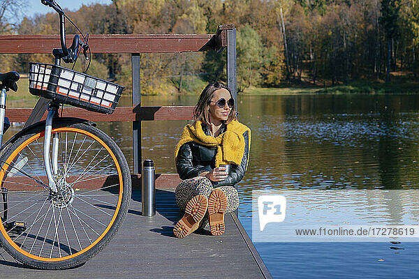Woman having coffee while relaxing on pier over lake