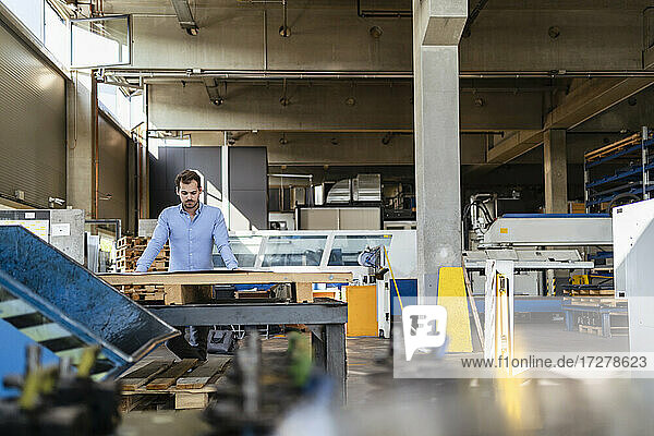Businessman working while standing by table at factory