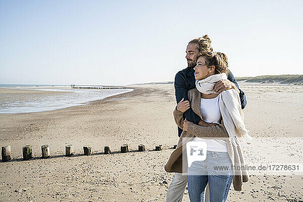 Young couple with eyes closed embracing while standing at beach against clear sky