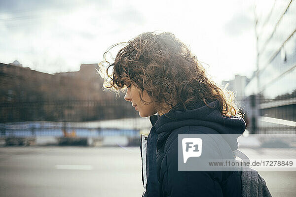 Woman with eyes closed standing by road at city