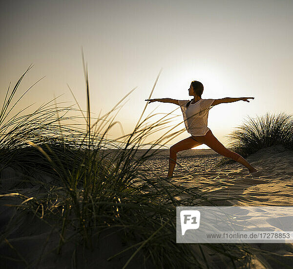 Young woman practicing warrior 2 position yoga at beach against clear sky during sunset